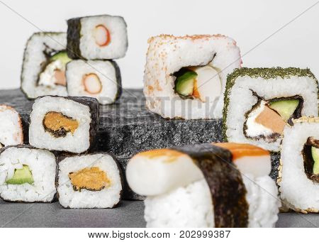 various sushi dishes on dark grey stone surface