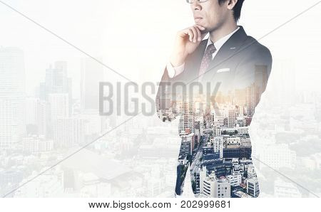 Asia business concept - thoughtful modern office man with dark suit stand and think the business plan. Double exposure effect with Japan city skyline background