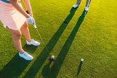 High-angle cropped view of a professional woman player holding the putter golf club, ready to hit the ball into the hole at the end of a difficult game with her partner or instructor poster