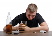 A sad young man is holding a big glass full of whiskey, isolated on a white background. A boozed guy with an alcoholic drink and a pack of cigarettes sitting at a wooden table. Alcoholism concept. poster