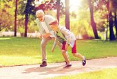 family, generation and people concept - happy grandfather and grandson racing at summer park poster