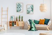Pineapples on rustic cupboard between ladder and beige sofa with green and orange pillows in living room poster