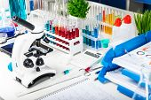 Creative abstract chemistry development medicine pharmacy biology biochemistry and research technology concept: table with scientific chemical laboratory equipment - microscope test tubes with color liquid substance samples vials flasks report documents e poster