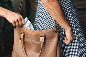 Pickpocket thief is stealing money from woman leather handbag poster