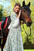 Beautiful young woman in medieval dress with a horse outdoor. poster
