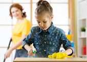 Happy family cleans the room. Mother and her child daughter do the cleaning in the house. A woman and a little kid girl wiped the dust and vacuumed the floor. poster