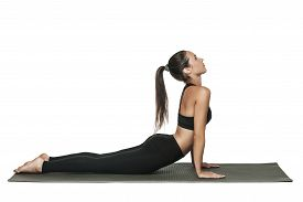 Young fit woman at yoga class. Attractive brunette woman with pony tail practicing yoga. Healthy lifestyle and sports concept. Series of exercise poses. Isolated on white.