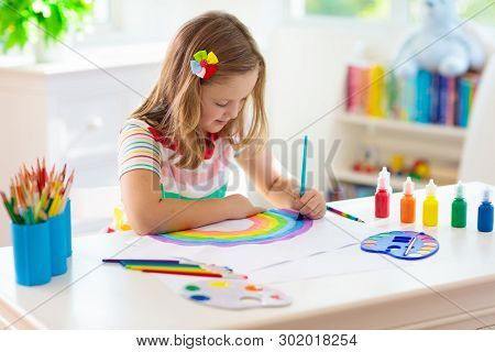 poster of Kids paint. Child painting in white sunny study room. Little girl drawing rainbow. School kid doing art homework. Arts and crafts for kids. Paint on children hands. Creative little artist at work.