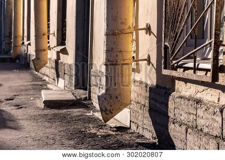 Old yellow drainpipes on a building wall in the morning sun. city street photography. empty street and rhythm downpipes poster