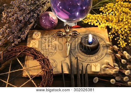 Pentagram, Runes, Black Candle And Magic Flowers With Open Book On Witch Table. Wicca, Esoteric, Div