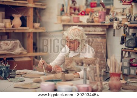 Nice Grey Haired Woman Concentrating In Her Work