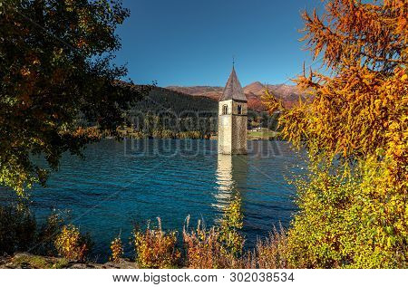 Wonderful Sunny Landscape. Amazing View Of The Lake Resia. Perfect Blue Sky Over The Azure Water In