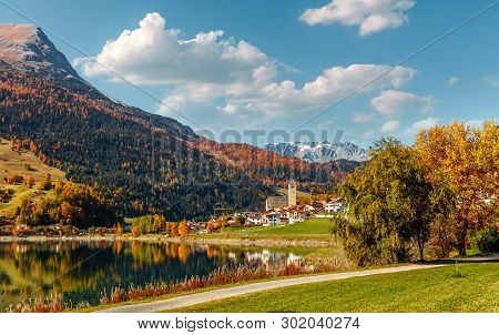 Awesome Alpine Highlands And Mountain Lake Resia In Sunny Day. Impressively Beautiful Autumn Of Ital