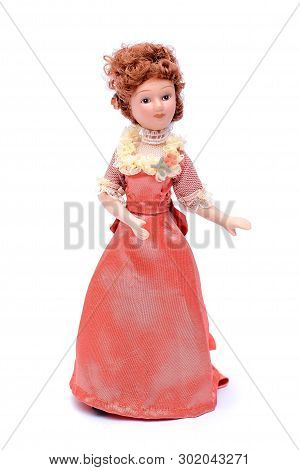 Beautiful Porcelain Doll With Red Hair In A Long Dressy Pink Vintage Dress, Isolate On White Backgro