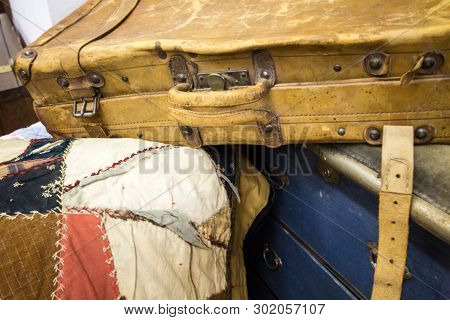Time For New Luggage.  Old Worn Leather Suitcase Sits Atop A Pile Of Retro Luggage.