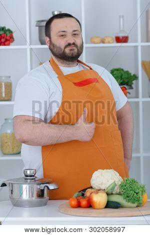 Portrait Of Cook Man Preparing Tasty Dish. Smiling Householder Wearing White Shirt And Orange Apron