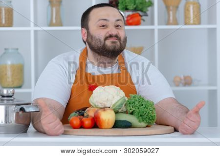 Portrait Of Guy Cooking Tasty And Dietetic Dinner. Smiling Man Sitting With Thumbs Up At Cuisine Sur