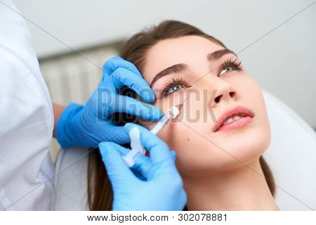 Doctor In Medical Gloves With Syringe Injects Botulinum Under Eyes For Rejuvenating Wrinkle Treatmen