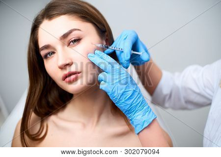 Beautician Doctor With Botulinum Toxin Syringe Making Injection To To Remove Crows Feet. Cheek Volum