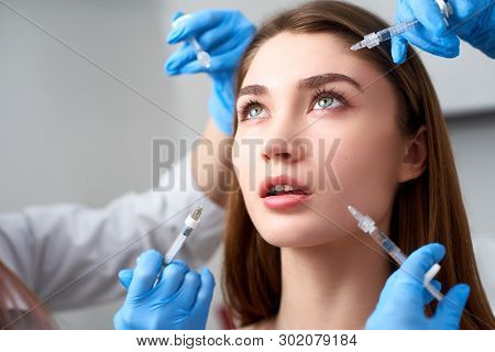 Hands Of Beauticians Holding Syringes Around Doll Like Woman Face For Injection In Cosmetology Clini