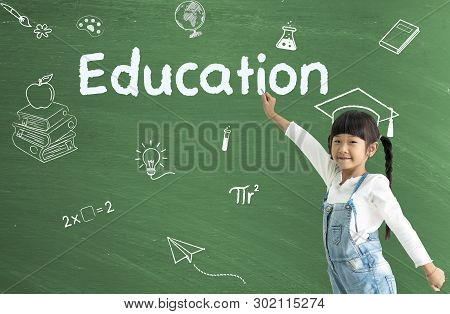 A Little Asian Girl Happy Smiling On Chalkboard Background. Education Concept.