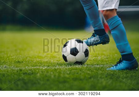 Close Up Of Legs And Feet Of Football Player In Blue Socks And Shoes Running And Dribbling With The