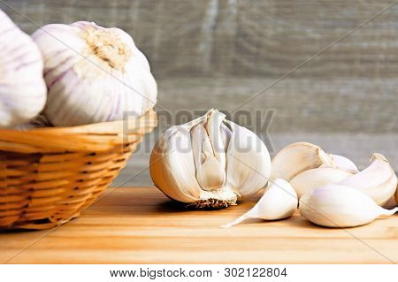 Garlic And Garlic Cloves On A Wooden Cutting Board