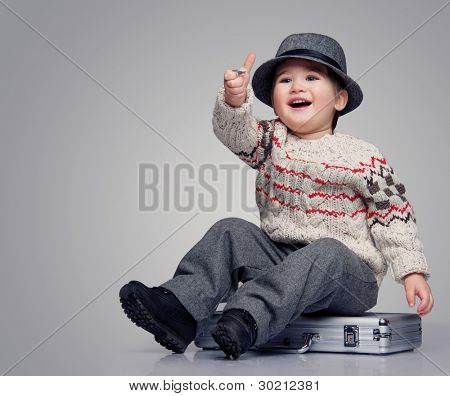 Smiling baby boy sitting on a suitcase.