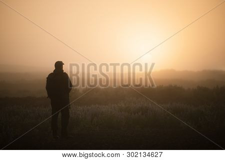 Tourist guy is standing and contemplating the misty dawn in Iceland. Beautiful light of the sun through the fog
