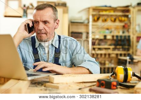 Portrait Of Modern Senior Carpenter Speaking By Phone And Using Laptop While Working In Joinery, Cop