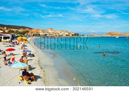 ILE-ROUSSE, FRANCE - SEPTEMBER 22, 2018: People sunbathing and bathing on the beach in Ile-Rousse, Corsica, France, with the Ile de la Pietra island on the right