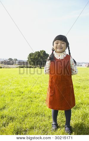 Young girl standing in meadow