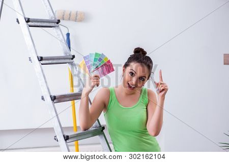 Young beautiful woman doing renovation at home