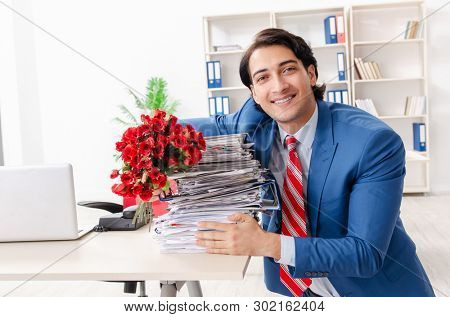 Young male employee with bunch of flowers in the office