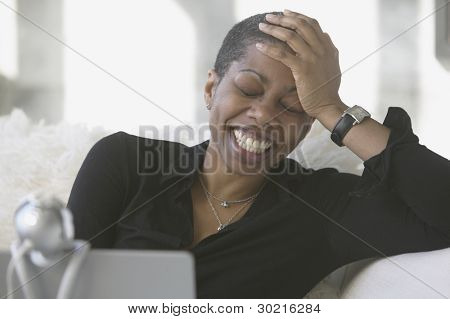 Woman laughing while using webcam
