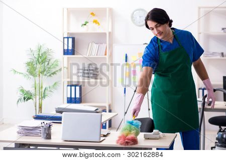 Male handsome professional cleaner working in the office