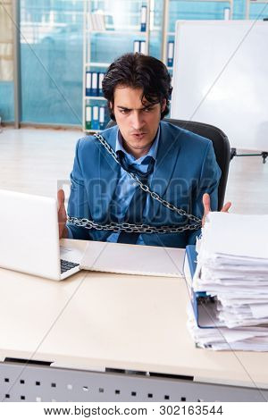 Chained male employee unhappy with excessive work