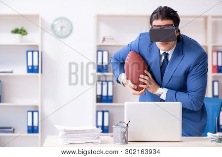 Young handsome businessman playing rugby with virtual glasses