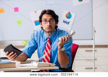 Young male financial manager working in the office