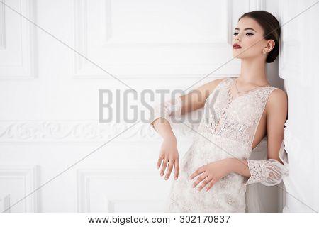 A portrait of a charming lady in a wedding dress posing in the studio. Wedding fashion, bride.
