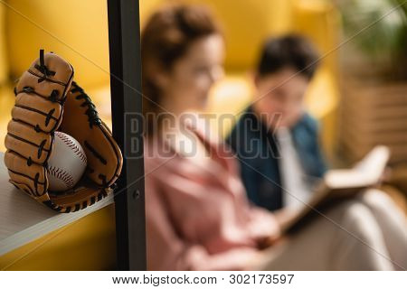 Selective Focus Of Baseball Glove And Ball Near Mother And Son Sitting On Floor And Reading Book Tog