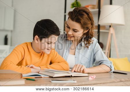 Smiling Mother Helping Adorable Son Doing Schoolwork At Home