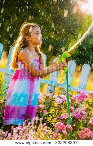 Playfull girl watering flowers with rain in the garden at summer day. Child using garden hose on sunny day at sunset lite. Little gardener playing in garden.