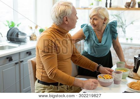 Happy Contended Beaming Nice-appealing Attractive Elderly Spouses Talking During Breakfast