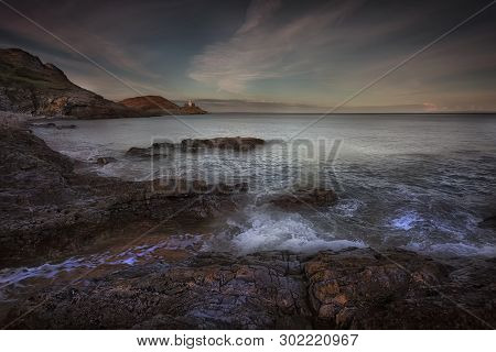 High Tide Over The Rocks At Dusk On Bracelet Bay And Mumbles Lighthouse On The Gower Peninsula In Sw