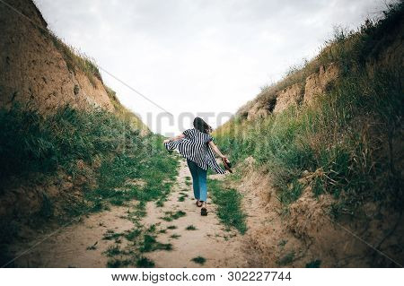 Stylish Hipster Girl Running On Sandy Cliff  To Sea And Holding Photo Camera.  Happy Young Boho Woma