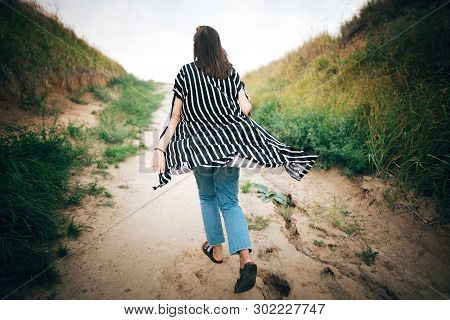 Stylish Hipster Girl Running To Sea Between Sandy Cliffs With Grass At Sunset. Happy Young Boho Woma