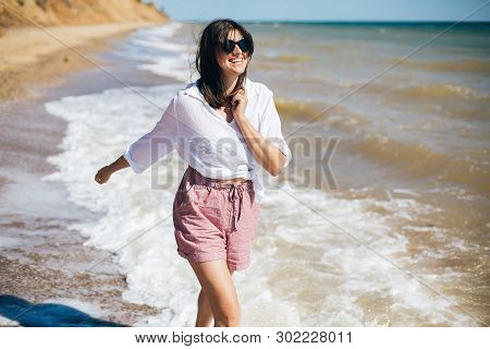 Happy Young Boho Woman Running And Smiling In Sea Waves In Sunny Warm Day On Tropical Island. Summer