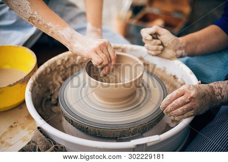 Hands Of Adult And Child Making Pottery, Working With Wet Clay Closeup. Process Of Making Bowl From