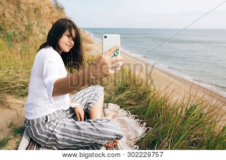 Stylish Hipster Girl Sitting On Beach And Holding Phone. Happy Boho Woman Practicing Yoga And Medita